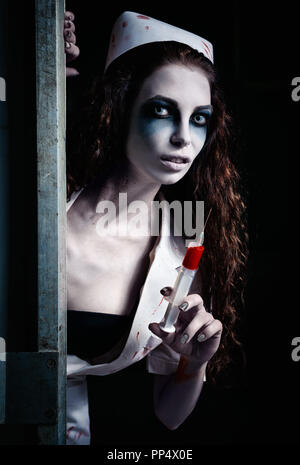 Horror shot: the terrible evil crazy nurse (doctor) with bloody syringe in hand. Zombie woman (living dead) - Stock Photo