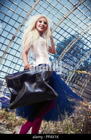 Portrait of the cute smiling freak girl with old suitcase. Attractive woman wearing corset, tights and tutu skirt in abandoned place - Stock Photo