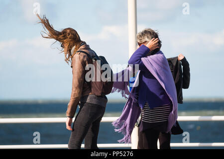 Aberystwyth, Wales, UK. Sunday 23rd Sept 2018.   UK Weather:  People walking along the promenade are windswept buffeted by the strong winds on a sunny but  blustery Equinox Sunday afternoon in Aberystwyth on the west wales coast. 