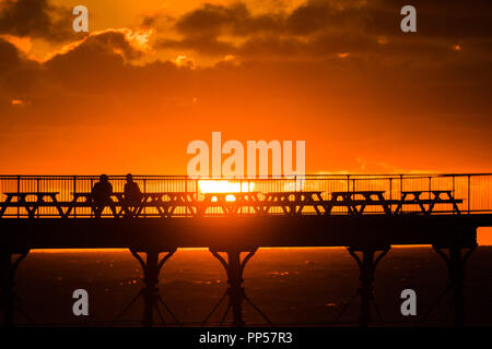 Aberystwyth Wales UK, Sunday 23 September 2018  UK Weather:  A fiery sunset over the seaside pier on Equinox Sunday evening in Aberystwyth on the west wales coast.  Today was the last day of Astronomical Summer - when the days and night are of equal lengths. From tomorrow the nights are longer than the days, marking  the onset of Astronomical Winter in the northern hemisphere  Photo © Keith Morris / Alamy Live News - Stock Photo