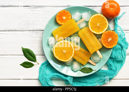 Orange Tangerine popsicles in blue plate with ice cubes and slices of fruit, white wooden rustic background. Top view, copy space - Stock Photo
