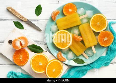 Orange Tangerine popsicles in blue plate with ice cubes and slices of fruit, white wooden rustic background. Top view, copy space,flat lay. - Stock Photo