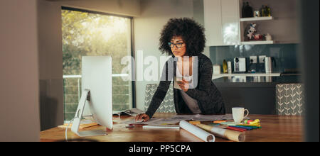Woman interior designer with color swatch in hand working on computer in the home office. Young african woman standing at the table and looking for a  - Stock Photo