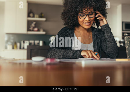 Portrait of happy young female interior designer looking at drawing and talking over smart phone. Young architect using phone at his workplace. - Stock Photo
