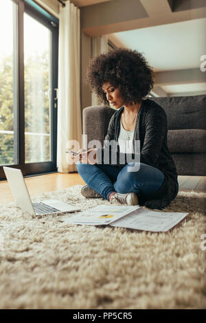 Business woman sitting on floor in living room with laptop and reports lying around texting on mobile phone. African female with curly hair using phon - Stock Photo