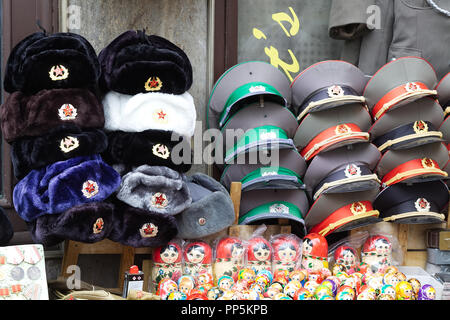 Russian and military caps on a stall in Berlin - Stock Photo
