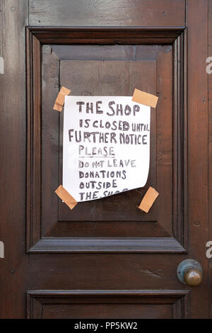 Hand written shop closed notice taped to door - Stock Photo