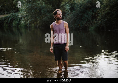 Portrait of bearded caucasian man standing in the middle of a river Stock Photo