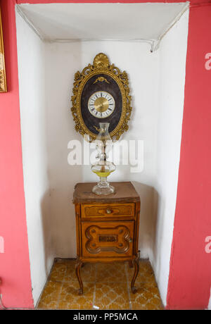 Classic wall clock, wooden cabinet and oil lamp or Quinque. Interior decoration of the Lola Vuela coffee shop. (Photo: Luis Gutierrez / NortePhoto.co - Stock Photo