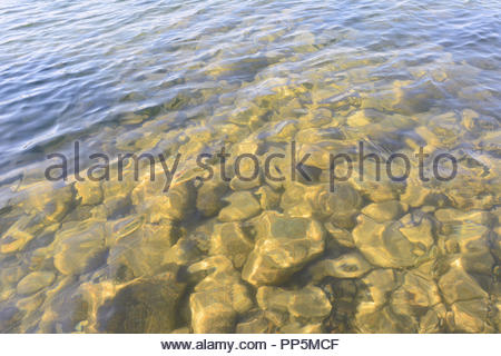 Sunlight shining on rocks under the surface of a lake in Canada. - Stock Photo