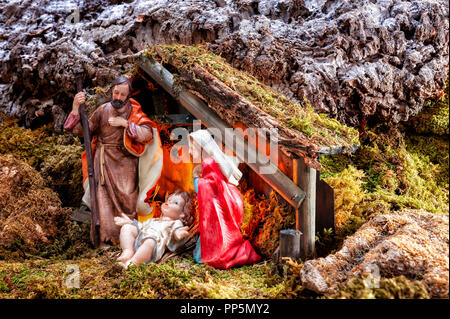 Close-up of the Christmas Nativity scene. Hut with baby Jesus in the manger, with Mary and Joseph. - Stock Photo
