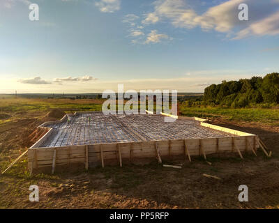 inspection well, trench and concrete slab of foundation with wooden formwork - Stock Photo