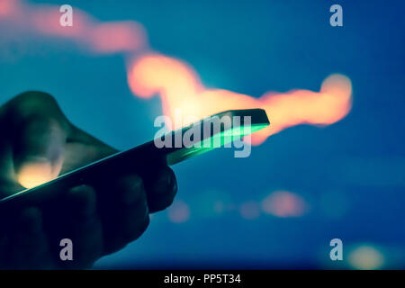 Trader in dark using mobile phone against stock market charts - Stock Photo