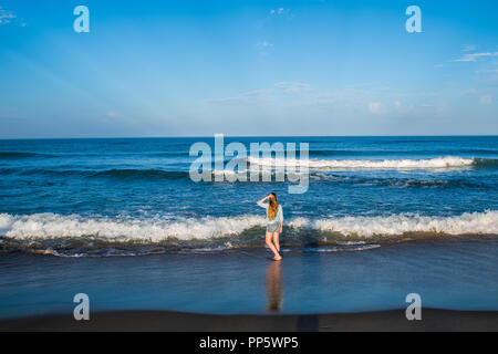 A little girl plays in the surf along the oceanfront of the outer banks in North Carolina - Stock Photo