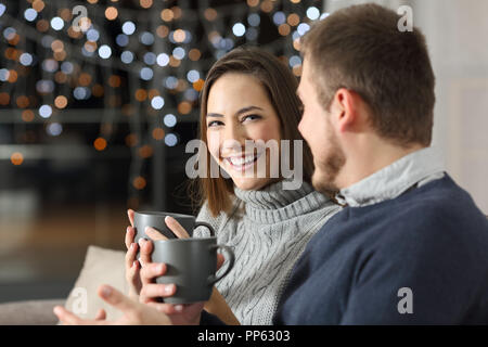 Couple talking in the night in winter sitting on a couch in the living room at home - Stock Photo