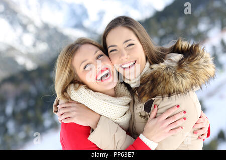 Happy friends cuddling and posing in winter holiday in a snowy mountain - Stock Photo