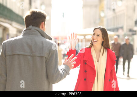 Two happy friends meeting and greeting in the street of a big city - Stock Photo