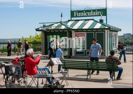 The upper level station of the Old Quebec Funicular, on the Dufferin Terrace. A local street performer entertains tourists with his trumpet. - Stock Photo