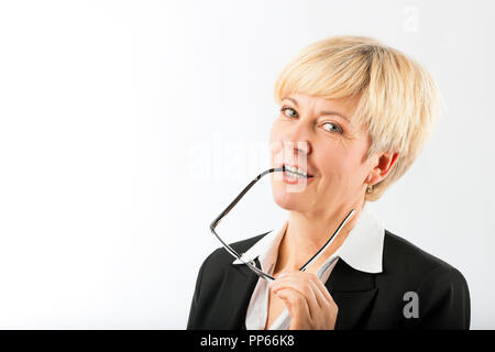 Mature businesswoman with eyeglasses earpiece in mouth - Stock Photo