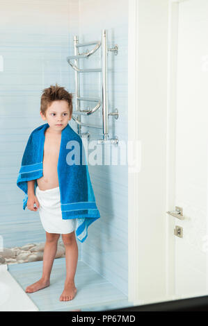 cute healthy little caucasian child with blue towel in bathroom - Stock Photo