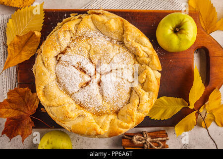 Traditional American apple pie on a wooden board, top view. Autumn food decor.