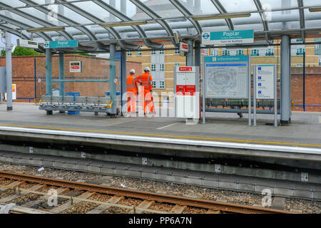 Poplar, London, UK - August 18, 2018: Two workmen dressed in high viz uniform in orange. Shows the workment waiting on the DLR platform for a train. - Stock Photo