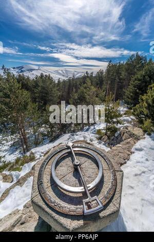 Penalara Natural Park winter scene. Old compass at 'Mirador de la Gitana' viewpoint covered with snow. Located in  Sierra de Guadarrama,  mountainous  - Stock Photo