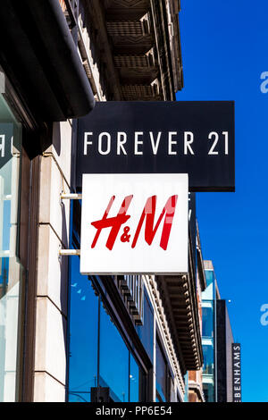 Signs for H&M and Forever 21 clothing brands and stores on Oxford Street, London, UK - Stock Photo