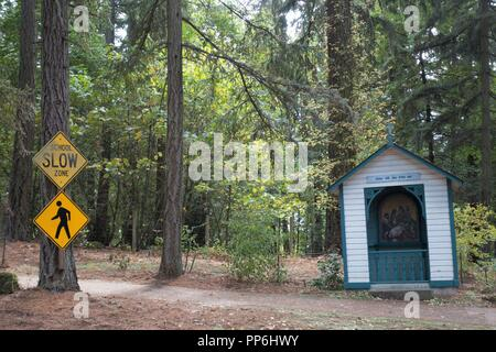 A caution, school zone sign near one of the stations of the cross at Mount Angel Abbey in Mount Angel, Oregon, USA. - Stock Photo