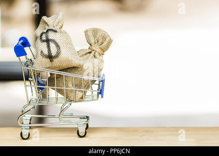 More shop for make money to shopping concept : US dollar in moneybag in small shopping cart on wooden table with copy space. Background for web shoppi