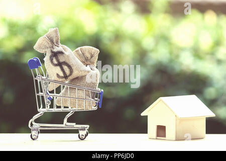 Home loan, mortgages, debt, savings money for home buying concept : US dollar money bag in shopping cart, residential, house on table against green na