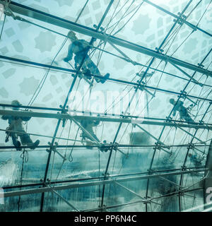 Window cleaners on the outside of curved airport windows, Dubai Airport. - Stock Photo