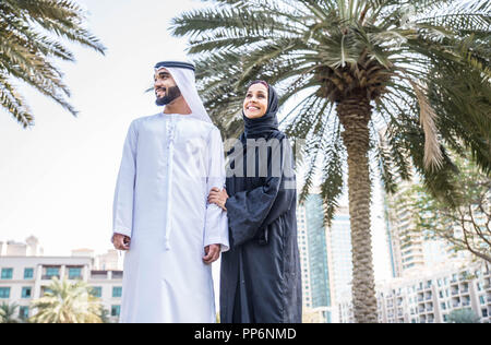 Arabic couple with traditional clothes dating outdoors - Stock Photo