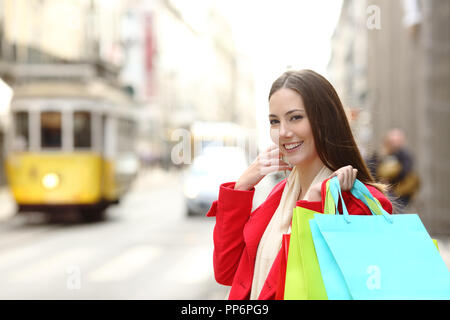 Happy shopper shopping holding colorful bags in a city old town - Stock Photo