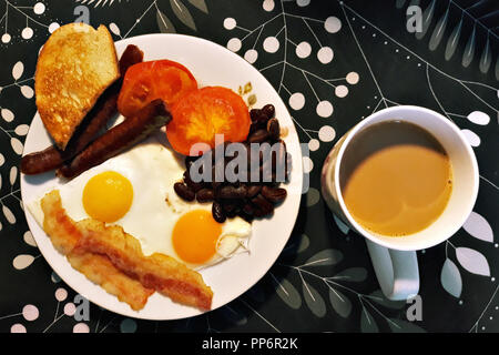 Plate with breakfast consisting of scrambled eggs, ham, sausages and beans and a nearby cup with hot aromatic coffee. - Stock Photo
