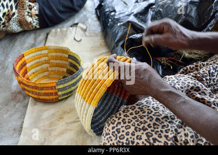 Woman weaving coiled baskets from pandanus palms at the Injalak Arts and Crafts Centre, Gunbalanya, Arnhem Land, Northern Territory, Top End,Australia - Stock Photo