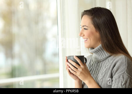 Side view portrait of a happy woman drinking coffee looking outside through a window at home - Stock Photo