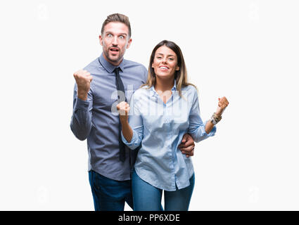 Young workers business couple over isolated background celebrating surprised and amazed for success with arms raised and open eyes. Winner concept. - Stock Photo