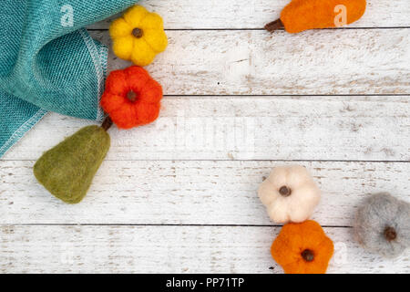 Flat lay autumn background with felt fuzzy pumpkins and gourds over a white wooden background. Fall concept with copy space - Stock Photo