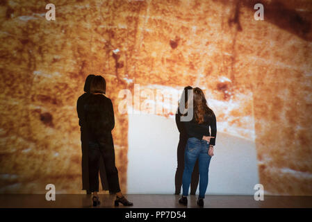London, UK.  24 September 2018. Staff members stand next to video works by Luke Willis Thompson.  Preview of an exhibition unveiling the four artists shortlisted for Turner Prize 2018 at Tate Britain. The exhibition is open 26 September to 6 January 2019.   Credit: Stephen Chung / Alamy Live News - Stock Photo