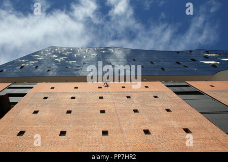 24 September 2018, Hamburg: A window cleaner hangs on ropes on the outer facade of the Elbphilharmonie as part of a rescue exercise of the special task force 'Höhenrettung Hamburg' (SEGH). The height rescuers rehearsed rescuing window cleaners at the Elbphilharmonie. Photo: Bodo Marks/dpa - Stock Photo
