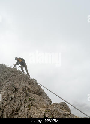 young attractive male mountain climber in the Dolomites of italy - Stock Photo