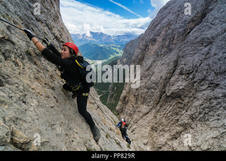 three mountain climbers on a Via Ferrata in the Dolomites in Alta Badia - Stock Photo