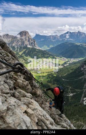 young pretty female mountain climber on a Via Ferrata in the Dolomites in Alta Badia - Stock Photo