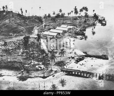 Guadalcanal-Tulagi Landings, 7-9 August 1942.  Wrecked facilities and aircraft at the Japanese seaplane base on Tanambogo Island, east of Tulagi. Photo is dated 8 August 1942 and was probably taken shortly before U.S. Marines captured the island. This view looks about west, with a burned-out pier in the foreground, fuel drums piled to the left and the wreckage of a seaplane among the trees in the center. The buildings are probably left over from the island's days as a Royal Australian Air Force facility. - Stock Photo