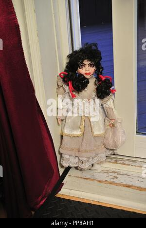 A creepy antique porcelain doll with long black hair and a scary, beautiful face with scars,,dressed in a white vintage dress, coming at you Halloween - Stock Photo