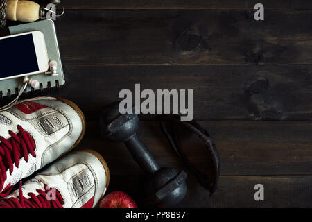 Fitness, healthy and active lifestyles Concept, Top view image of old sport shoes, smart phone with headphones, jumping rope, dumbbell, sport glasses  - Stock Photo