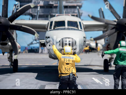 180919-N-FA806-0081 ATLANTIC OCEAN (Sept. 19, 2018) Aviation Boatswain's Mate (Handling) 3rd Class Tatsiyana Carter, from Covington, Georgia, directs an E-2C Hawkeye, assigned to Carrier Airborne Early Warning Squadron (VAW) 120, on the flight deck aboard the aircraft carrier USS George H.W. Bush (CVN 77). GHWB is underway in the Atlantic Ocean conducting routine training exercises to maintain carrier readiness. (U.S. Navy photo by Mass Communication Specialist 3rd Class Roland John) - Stock Photo