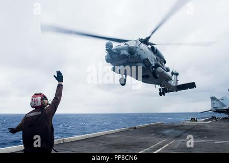 180920-N-OY799-0047 PHILIPPINE SEA (September 20, 2018) A Sailor assigned to Helicopter Maritime Strike Squadron (HSM) 77 directs an MH-60R Sea Hawk as it launches from the flight deck of the Navy's forward-deployed aircraft carrier USS Ronald Reagan (CVN 76) during Valiant Shield 2018. The biennial, U.S. only, field-training exercise focuses on integration of joint training among the U.S. Navy, Air Force and Marine Corps. This is the seventh exercise in the Valiant Shield series that began in 2006. (U.S. Navy photo by Mass Communication Specialist 2nd Class Kenneth Abbate) - Stock Photo