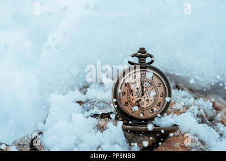 New year clock before midnight. Antique pocket watch in the snow - Stock Photo